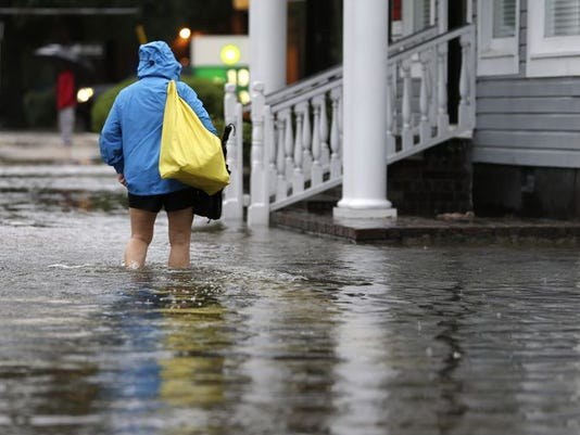 A woman walks down a flooded sidewalk toward an open convenience store in Charleston, S.C., Sunday, Oct. 4, 2015. President Barack Obama declared a state of emergency in South Carolina and ordered federal aid to bolster state and local efforts as flood warnings remained in effect for many parts of the East Coast through Sunday.
