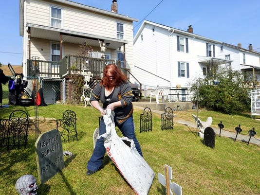 "Tasha Shupp of York drags a bag of mulch to spread on ""graves"" marked by decorative tombstones in her friend Heather Bennett's backyard."