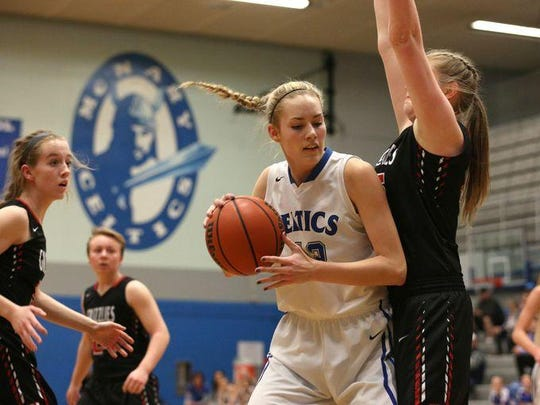 McNary senior Reina Strand (42) pushes up against a McMinnville defender on Friday, Jan. 22, 2016 at McNary High School in Keizer.