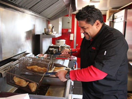 Carlos Serrano, aka The Empanada Guy, who owns several food trucks plus a freestanding restaurant in Freehold, prepares empanadas inside one of his food trucks set up in Port Reading section of Woodbridge, NJ Wednesday March 18, 2015.