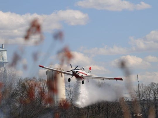 A forest fire service plane makes a water drop to knock back the fire.
