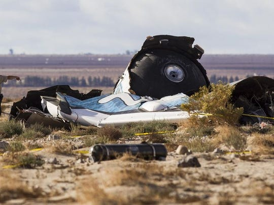 Law enforcement officers take a closer look at the wreckage near the site where a Virgin Galactic space tourism rocket, SpaceShipTwo, exploded and crashed Oct. 31.