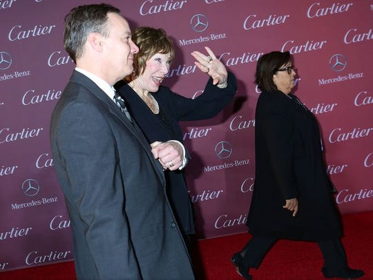 Shirley McLaine dashes by the paparazzi on the red carpet at the Palm Springs International Film Festival.