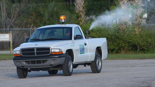A St. Lucie County Mosquito Control truck turns on its sprayer as it heads out from the compound in Fort Pierce on an evening run in St. Lucie County in 2002.