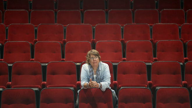 Zoe Bradford sits in the midst of empty chairs at the Company Theater in Norwell which she co-founded forty one years ago that has been empty as a result of the pandemic.