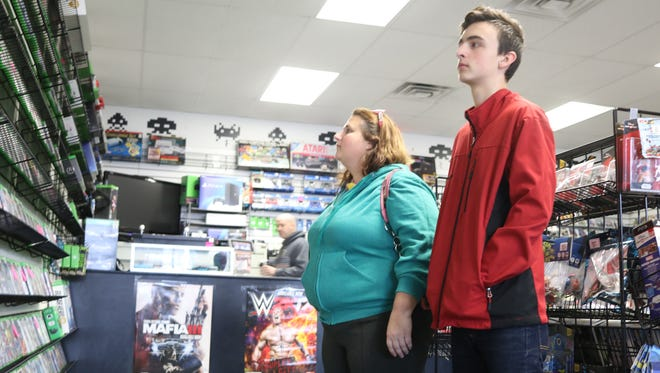 Joanie Hatt and Cameron Crandall shop for video games at C&C Games, a local family-owned game retailer in Port Clinton.