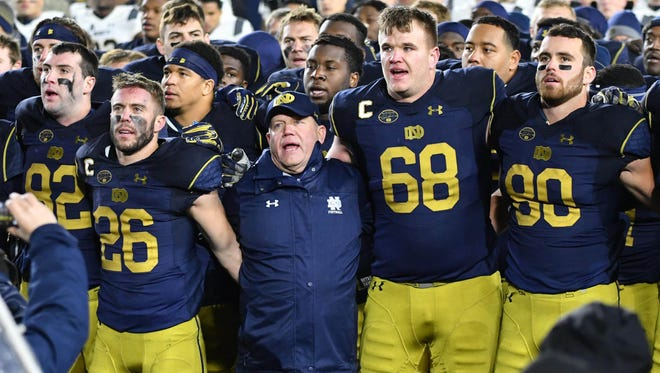 Nov 18, 2017; South Bend, IN, USA; Notre Dame Fighting Irish head coach Brian Kelly sings the Notre Dame Alma Mater with wide receiver Austin Webster (26) offensive lineman Mike McGlinchey (68) and tight end Durham Smythe (80) after Notre Dame defeated the Navy Midshipmen at Notre Dame Stadium. Mandatory Credit: Matt Cashore-USA TODAY Sports