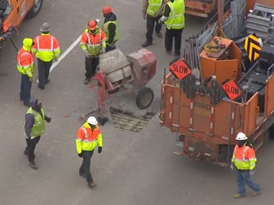 Crews patch a pothole on the Rouge Bridge on I-75 March