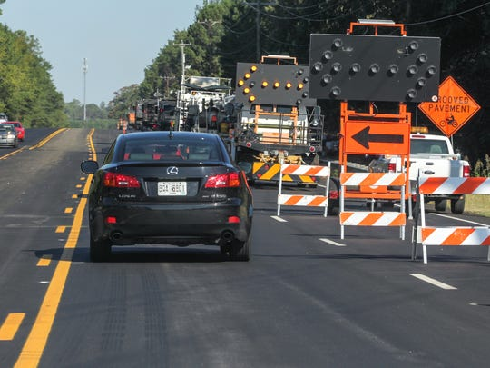Cars drive on newly laid asphalt Thursday on U.S. 76 in Pendleton next to construction workers adding more near the S.C. 187 intersection.