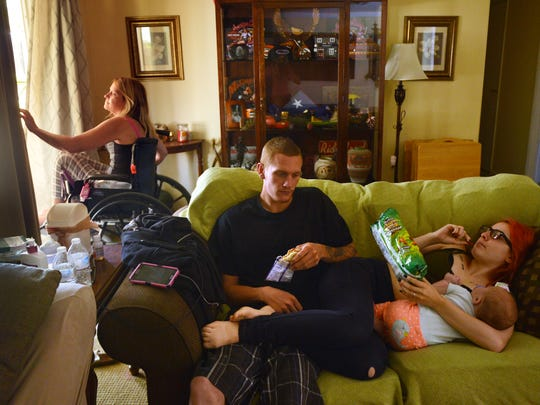 Marcy Majer wheels out a sliding glass door as her son Adam Majer, his fiancée,  Emily Cervantes, and their baby, Addison Majer, keep her company.