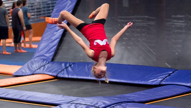 """10-year-old GiGi Molloy does a backflip at Sky Zone, which will host a """"Tramp Out Cancer"""" fundraiser."""