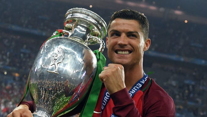 Cristiano Ronaldo carries the European Championship trophy on Sunday.