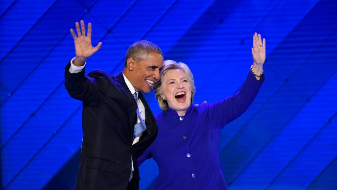 President Barack Obama stands with Hillary Clinton after Obama spoke during the 2016 Democratic National Convention at Wells Fargo Center.