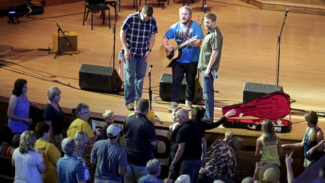 Walt Hamburger (center) performs Sunday at the Lawrence Memorial Chapel while members of the audience hand off donations. More than $3,000 was raised for two Neenah animal shelters during Mile of Music.