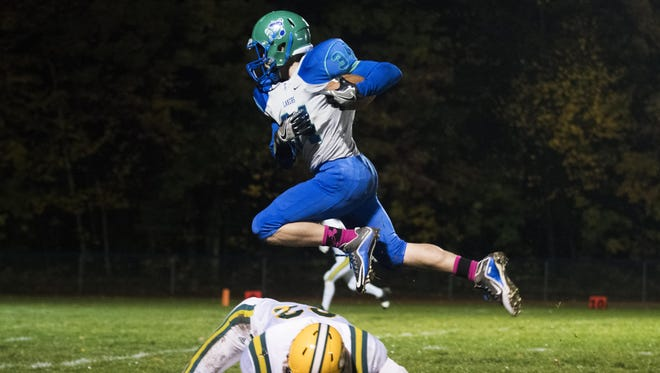 Colchester's Matt Hesford (34) leaps over BFA-St. Albans' Jarrett Gamache (32) during the high school football game between at Colchester High School on Friday night.