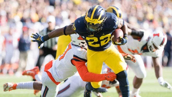 Michigan running back Karan Higdon fights his way through an attempted tackle against Illinois.