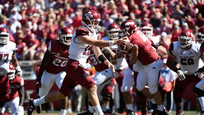 New Mexico State quarterback Tyler Rogers slips past the Arkansas defense to score a touchdown during the first half of an NCAA college football game in Fayetteville, Ark., Saturday.