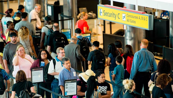 Travelers wait in line at a security checkpoint at Baltimore/Washington International Airport on June 29, 2017.