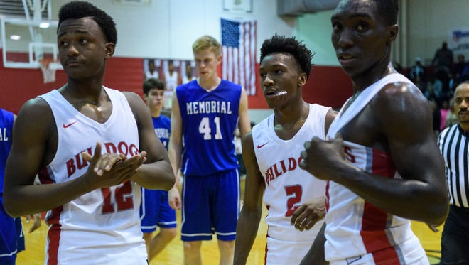 Bosse's E'Deviyon Cooper (12), Mekhi Lairy (2) and DeAngelo Ware (3) walk towards the bench after Lairy broke the school's top scoring record in the fourth quarter against the Memorial Tigers at Bosse High School in Evansville, Ind., Tuesday, Dec. 12, 2017. The Bulldogs defeated the Tigers, 85-59.