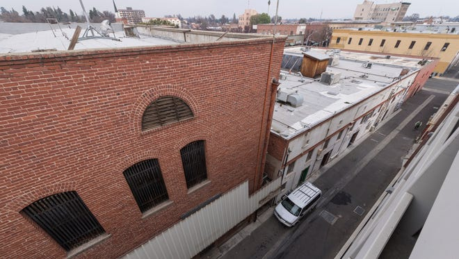 Downtown Visalia is looking to increase access to second-story businesses by adding a pedestrian bridge over the alley between the Acequia Street parking structure, right, and West Main Street businesses. Photo taken Friday, January 12, 2018.