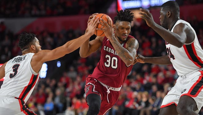 South Carolina Gamecocks forward Chris Silva (30) is defended by Georgia Bulldogs guard Juwan Parker (3) and forward Derek Ogbeide (34) during the first half Saturday afternoon at Stegeman Coliseum.