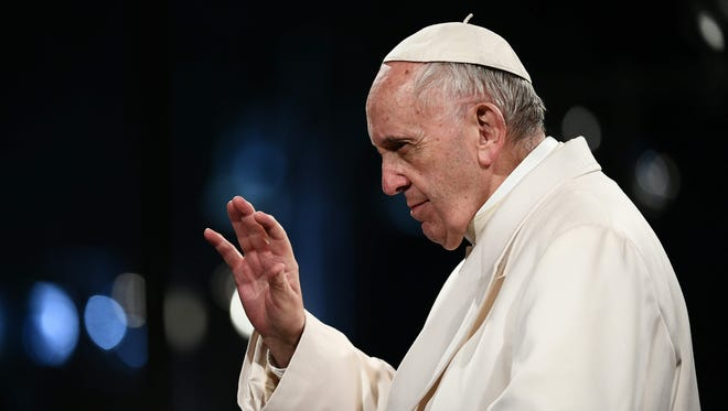Pope Francis waves to the crowd at the end of the Via Crucis (Way of the Cross) torchlight procession at the Colosseum on Good Friday in Rome.