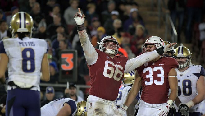 Stanford Cardinal defensive tackle Harrison Phillips (66) and linebacker Mike Tyler (33) celebrate during an NCAA football game against the Washington Huskies at Stanford Stadium. Stanford defeated Washington 30-22.