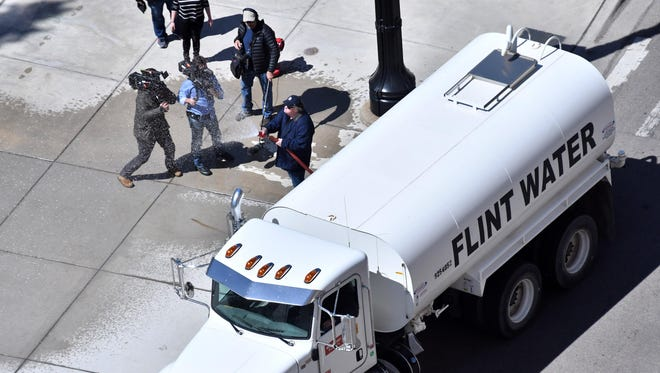 """Michael Moore showed up Friday in front of the Michigan Capitol with a tanker truck labeled """"Flint water"""" that squirts water on the lawn and sidewalks. Surrounded by a film crew, Moore set up shots for a future project that he and crews declined to discuss."""