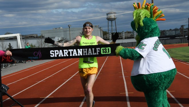 Alex Hampel of Middletown, Delaware, crosses the finish line first in the third annual Spartan Half Marathon.