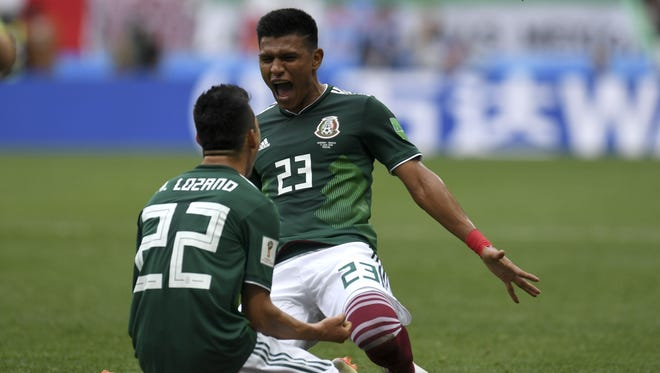 Mexico's forward Hirving Lozano (left) celebrates with teammate Jesus Gallardo  after scoring a goal during the World Cup match against Germany.