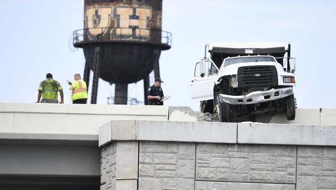 A Tennessee Department of Transportation dump truck dangles over the edge of Interstate 40 in downtown Nashville on Friday, June 22, 2018.