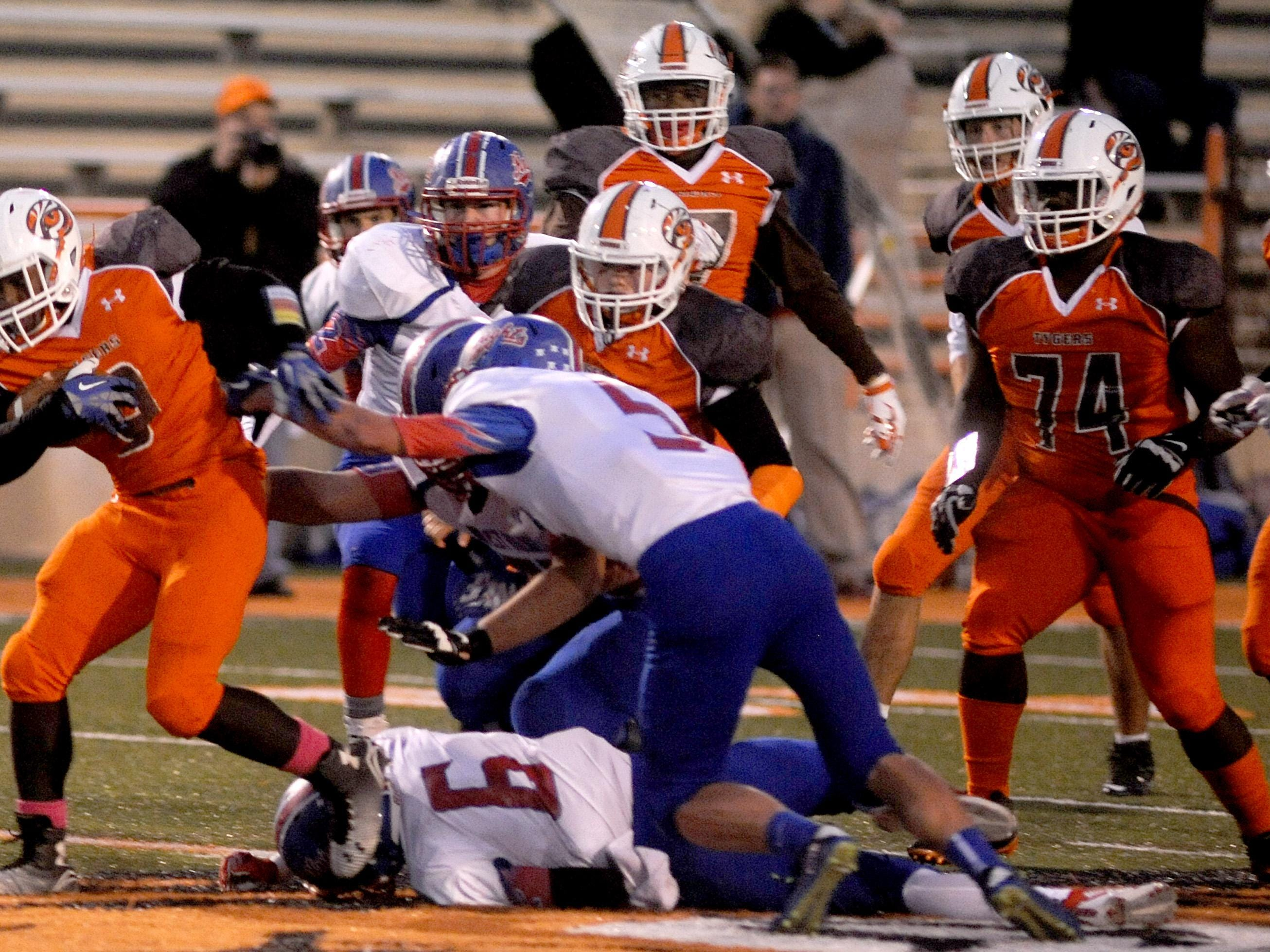 Mansfield Senior's Brian Benson steps on the helmet of Trenton Bridenthal of West Holmes as Benson breaks free for a long touchdown run Friday night at Arlin Field. The Tygers have a shot of climbing into first place in the Ohio Cardinal Conference when they travel to league-leading Wooster Friday.