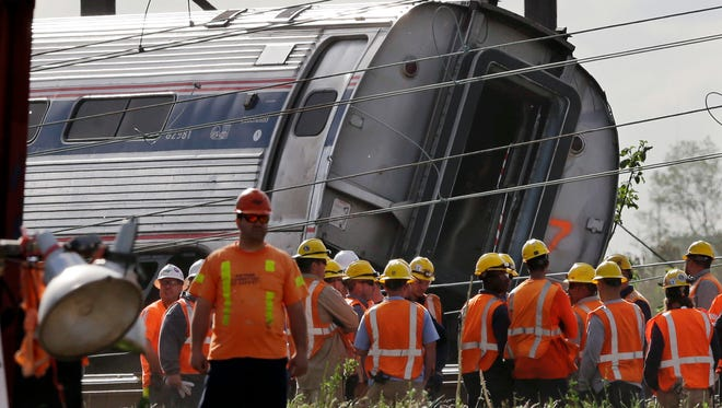 Emergency personnel gather near the scene of a deadly train derailment, Wednesday in Philadelphia. The Amtrak train, headed to New York City, derailed and crashed in Philadelphia on Tuesday night, killing at least six people and injuring dozens of others.