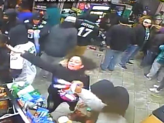 A woman throws merchandise as a crowd of Eagles fans