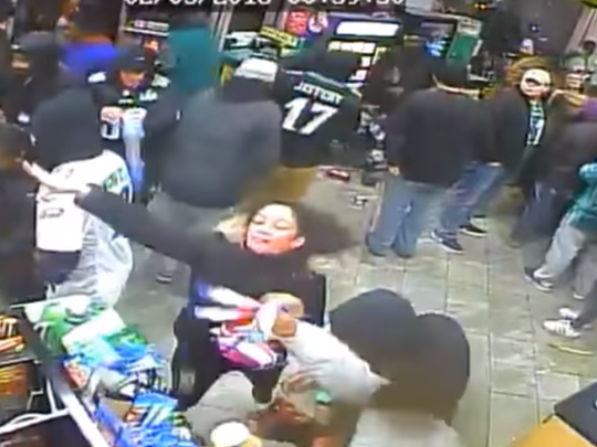 A woman throws merchandise as a crowd of Eagles fans trashes a South Philadelphia convenience store after Sunday night's Super Bowl,.