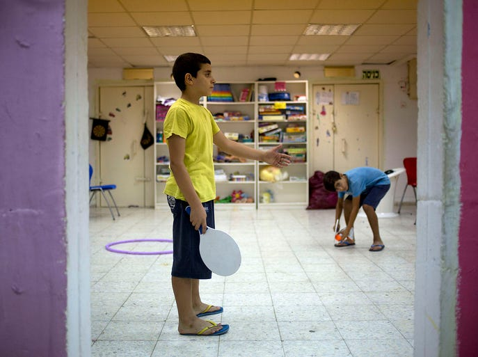 Children play in a public bomb shelter on July 16 in a residential area in Sderot, southern Israel. The structures are built to resist incoming artillery fire and include play areas.