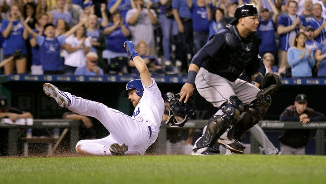 Kansas City Royals' Ben Zobrist slides past Seattle Mariners catcher Jesus Sucre as he score on a throwing error by Sucre during the first inning of a baseball game Thursday, Sept. 24, 2015, in Kansas City, Mo.