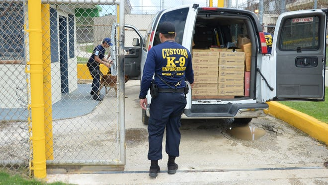 In this Sept. 25, 2017, file photo, Guam Customs and Quarantine's K-9 Drug Detector Unit checks vehicles going into Department of Corrections Mangilao facility for illegal substances.