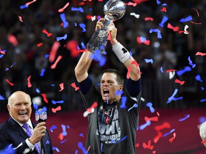 New England Patriots quarterback Tom Brady raises the
