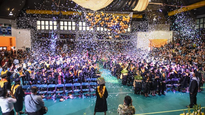 Balloons fall and confetti fills the air after the traditional turning of the tassel by 210 Titans during Tiyan High School Class of 2017 commencement exercise at the Calvo Field House at the University of Guam in Mangilao on Thursday, June 8, 2017.