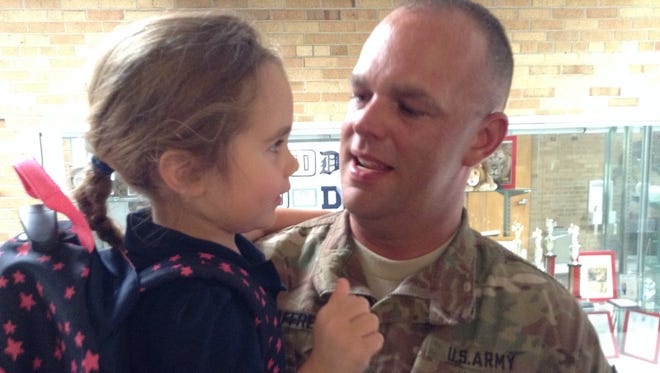 Coraline McAffrey talks  with her father National Guard Sgt. Levon McAffrey, who just returned from a deployment to Iraq.