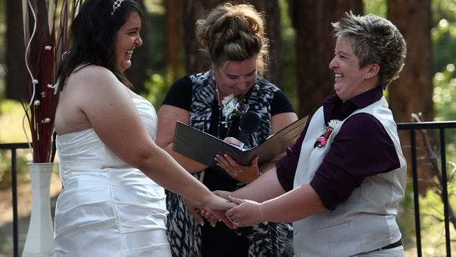 Angie Thompson, right, and Veronica Crew share a laugh while getting married at the Galena Creek Fish Hatchery near Reno on June 26, 2015.
