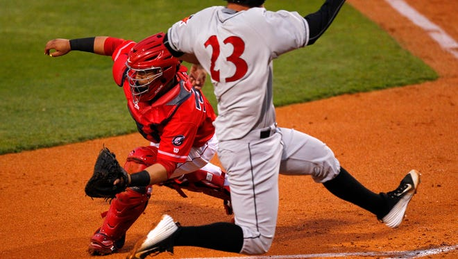 Indianapolis Indians' Jacob Stallings (23) slides in safe at home plate ahead of the tag by Louisville Bats' catcher Ramon Cabrera (38) during the fourth inning at Louisville Slugger Field in Louisville, Kentucky.         April 21, 2016