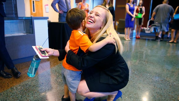 Rachel Bennett Yanof receives a hug from her son Bennett, prior to the first graduation ceremony for Phoenix Collegiate Academy Tuesday, May 24, 2016, in Phoenix. Seven years ago, Yanof went door to door in a poor neighborhood in South Phoenix and promised parents that if they sent their kids to her new charter school, they would go to college. Every one of the 25 students in her senior class, is going to college or to some sort of higher education.
