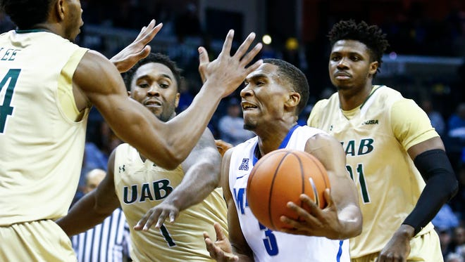 University of Memphis guard Jeremiah Martin (middle) drives to the basket against the UAB defense during second half action at the FedExForum.