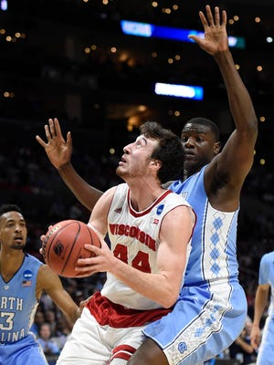 Wisconsin Badgers forward Frank Kaminsky (44) moves to the basket against North Carolina Tar Heels forward Joel James (42) during the first half in the semifinals of the west regional of the 2015 NCAA Tournament at Staples Center.