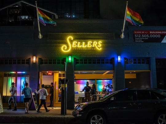 People pass by Sellers Underground in Austin June 20, which reopened after Gov. Greg Abbott lifted orders keeping bars closed.