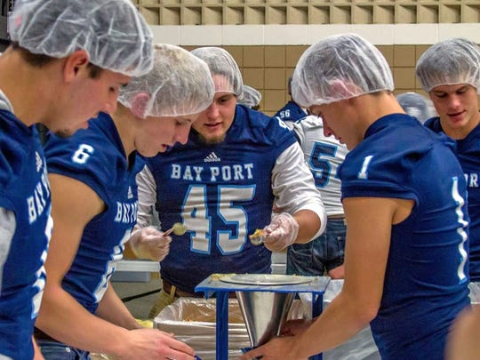 Football players from Bay Port High School volunteer