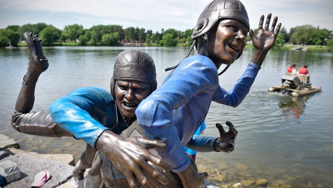 """Paddleboats pass by a new sculpture named """"Hey Mary Lou!"""" that has been installed on the shore of Lake George in St. Cloud. The sculpture is one of twelve to be installed as part of a sculpture walk in the downtown and Lake George areas."""
