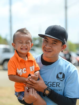Outrigger player Steven Nedlic takes a picture with his son Devan Ray, 1, during his GHRA Softball League game at Tiyan Softball Field on Feb. 27.